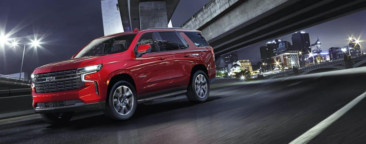 A red 2021 Chevy Tahoe RST is shown driving under a bridge at night.