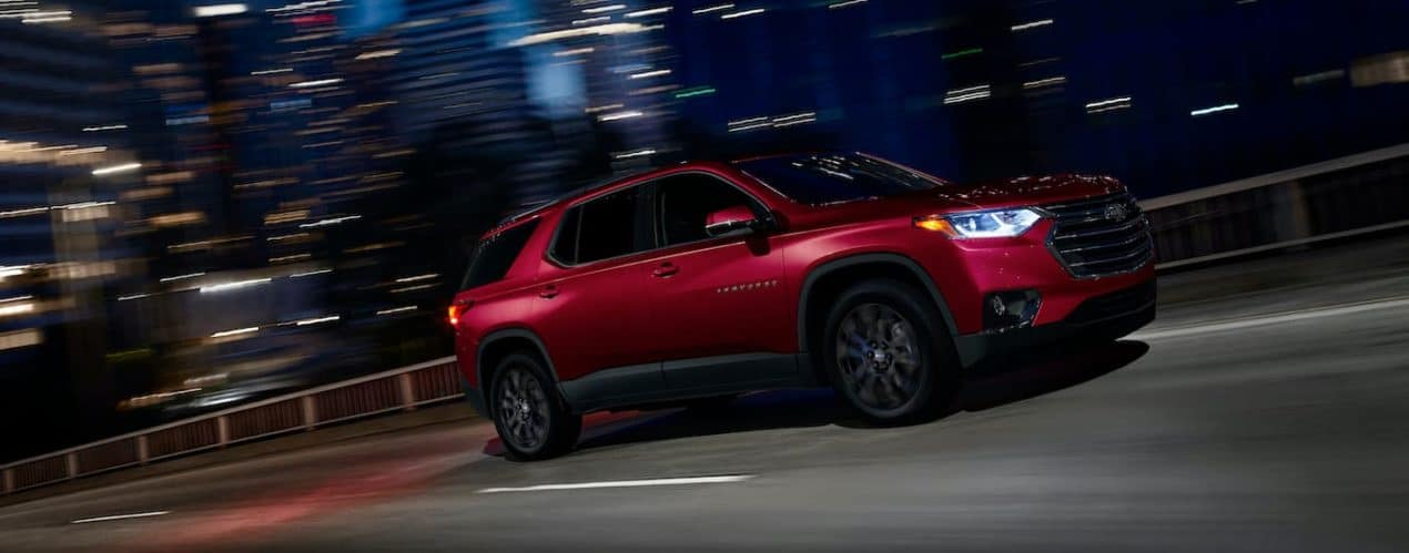 A red 2021 Chevy Traverse RS is shown from the side driving through a city at night.