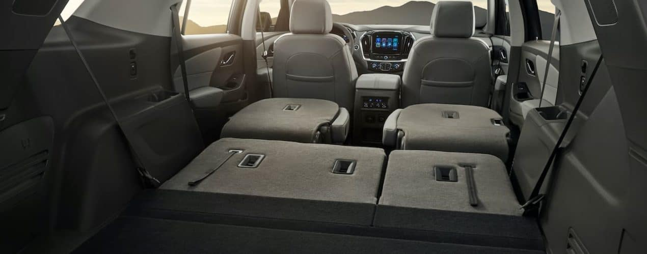 The black interior and three row seating is shown from the rear in a 2021 Chevy Traverse.