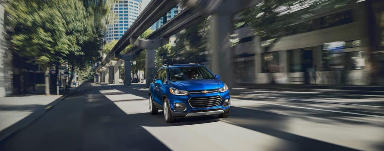 A blue 2021 Chevy Trax is shown driving down a city street under elevated train tracks.
