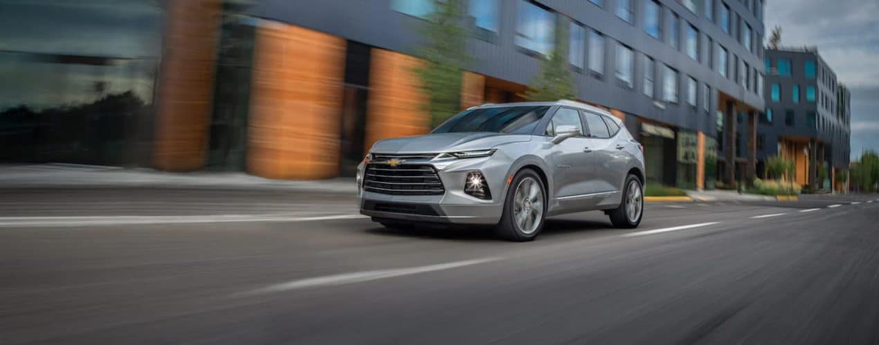 A silver 2021 Chevy Blazer Premier is shown from the side driving through a city.