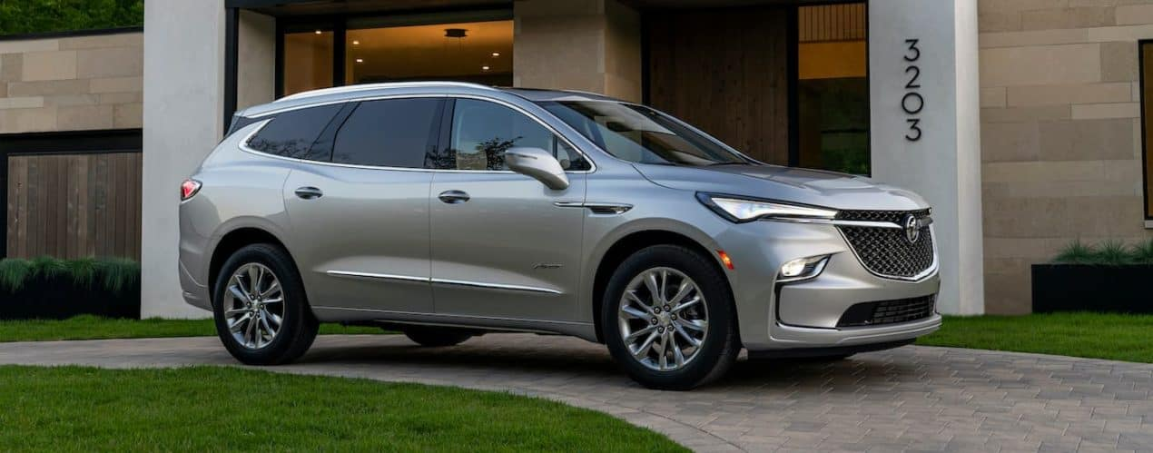 A silver 2022 Buick Enclave Avenir is shown parked in front of a modern house.
