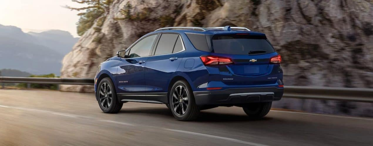 a blue 2022 Chevy Equinox is shown from the back driving on an open road.