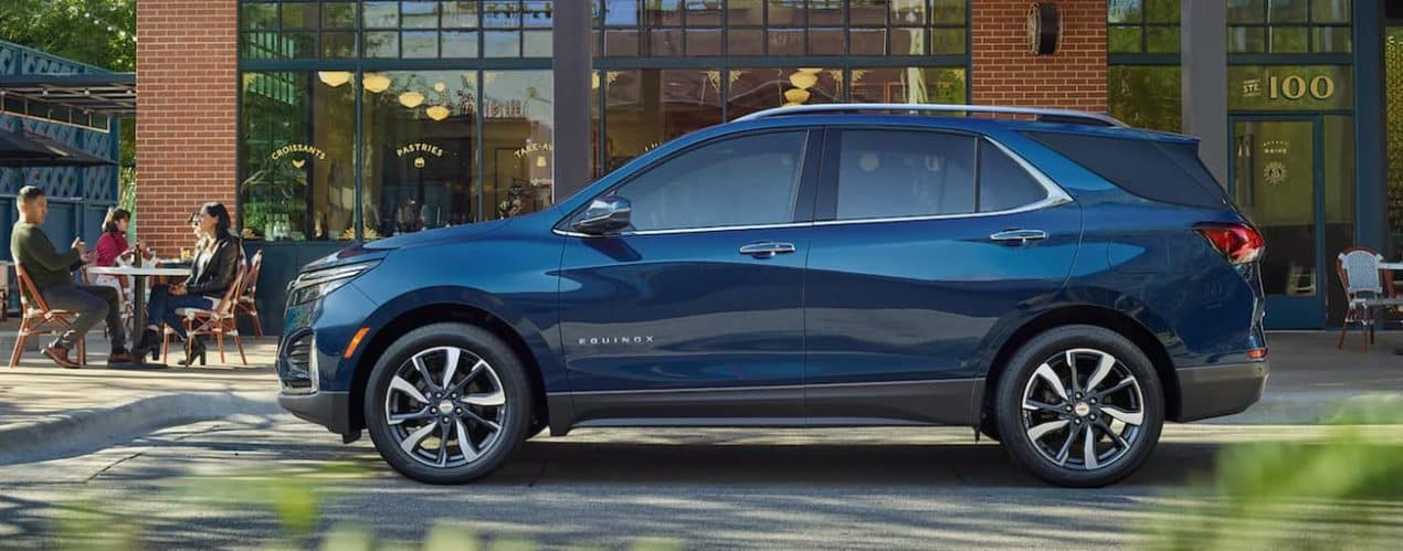 A blue 2022 Chevy Equinox is shown parked in front of a building.