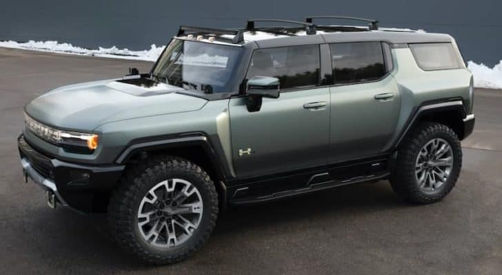 A light green 2023 GMC Hummer EV SUV is angled left in a parking lot.