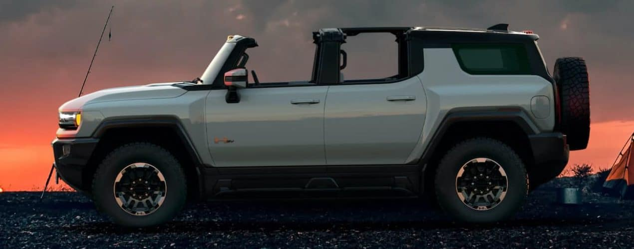 A white 2023 GMC Hummer EV SUV is shown from the side at sunset at a campsite.