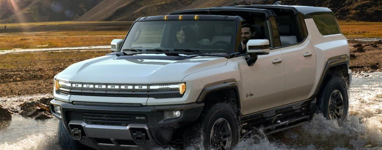 A white 2023 GMC Hummer EV SUV is off-roading in a river.