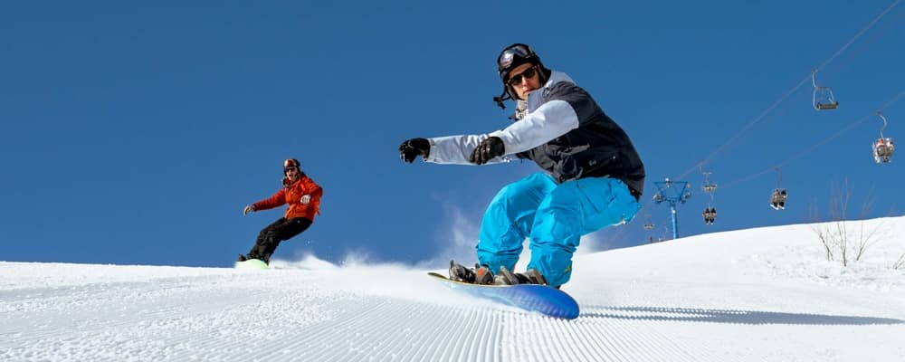 Two snowboarder riding on ski slope_105115404