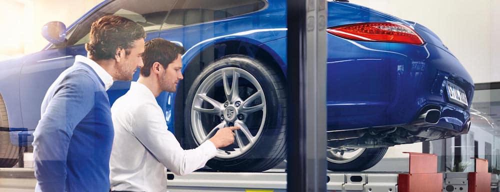 Porsche service adviser and customer examining tires