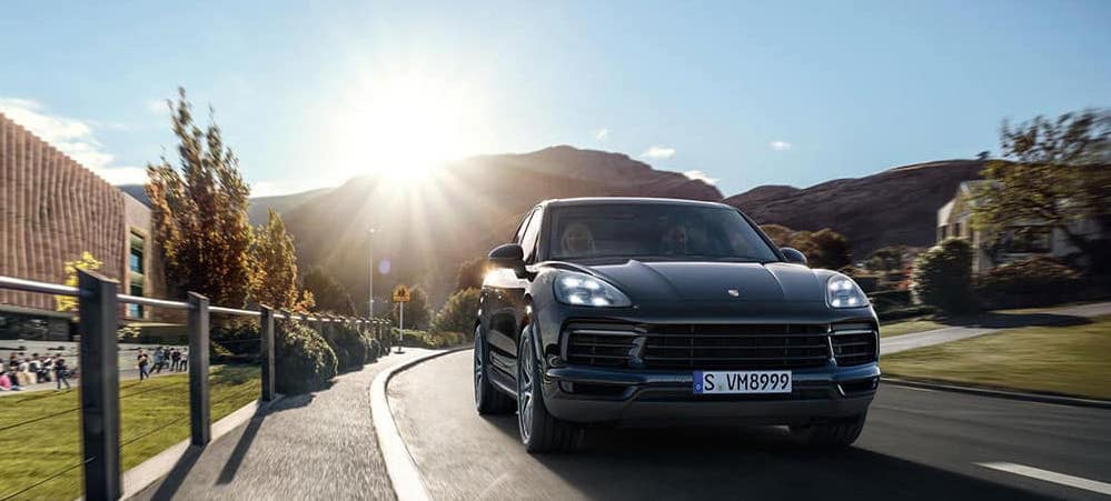 Black Porsche Cayenne driving with mountains and sun behind it