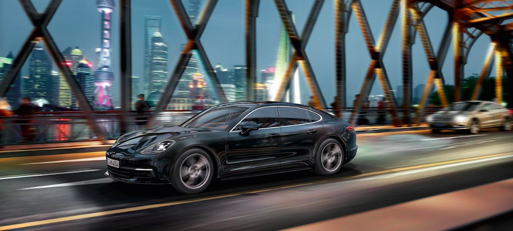 Porsche Panamera driving across city bridge at night