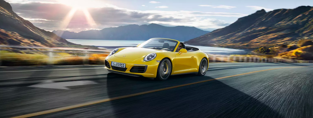Yellow Porsche 911 convertible driving down highway