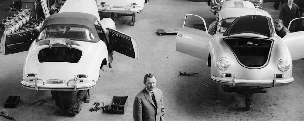 Black and white photo of Ferdinand Anton Ernst Porsche standing in Porsche factory