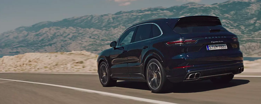 Porsche Cayenne cruising down highway in the desert