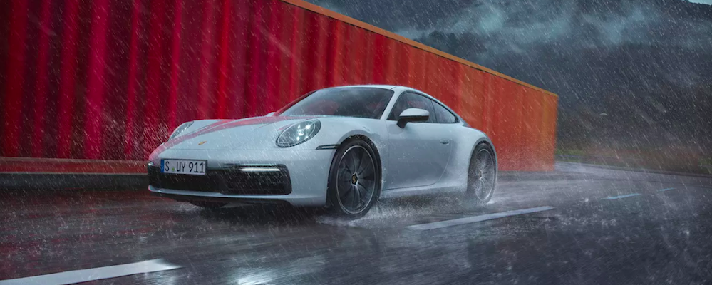 Porsche 911 driving past storage container in raining weather