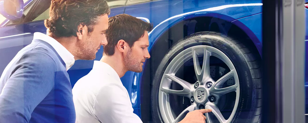 Service advisor and customer examining wheel on blue Porsche on lift