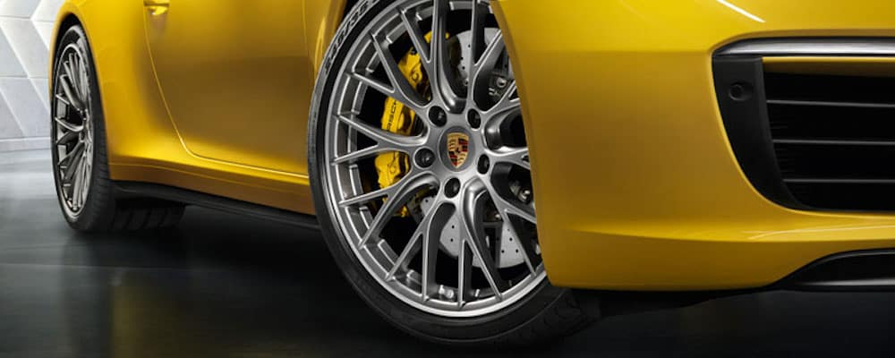 Close up of passenger side wheels on yellow Porsche 911