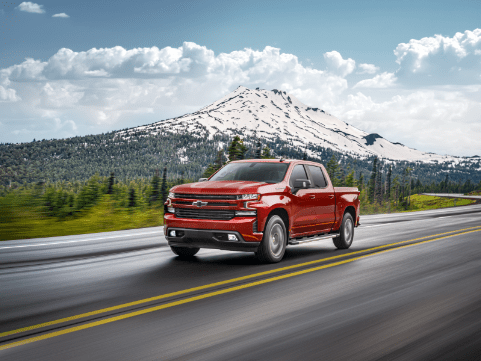 https://di-uploads-pod3.dealerinspire.com/progressivechevy/uploads/2020/03/red-chevy-silverado.png driving by snow capped mountains