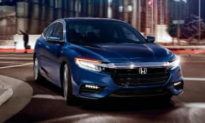 A blue 2018 Honda Insight taking a corner in a city at night