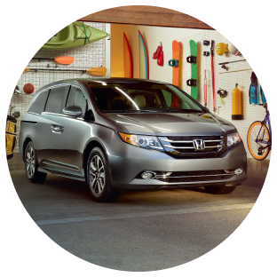 A gray Honda Odyssey in a garage filled with adventure gear