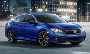 A blue 2019 Honda Civic in front of a city at night