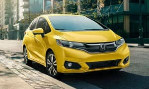 A yellow 2019 Honda Fit parked on a city street