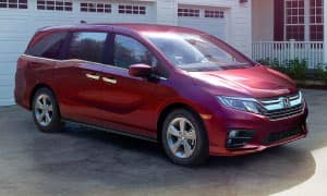 A red 2019 Honda Odyssey in front of a suburban house