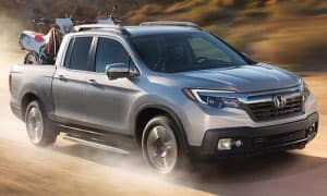 A silver 2019 Honda Ridgeline driving a dirt road with a dirtbike in the bed