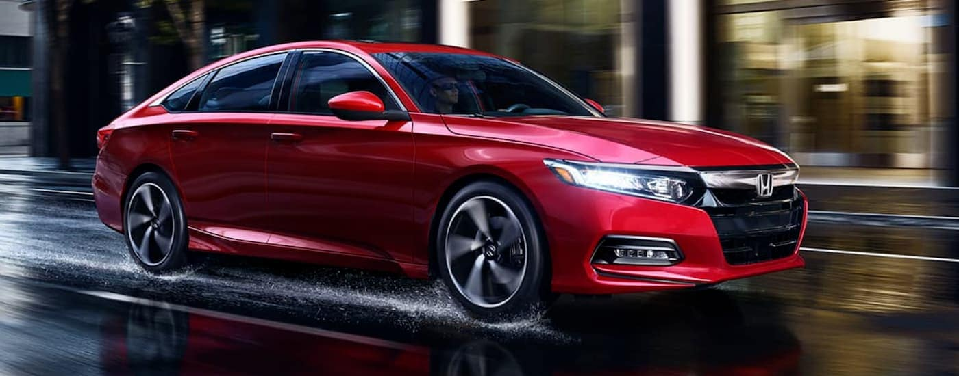 A red 2020 Honda Accord Sport 2.0T is driving in the rain at night near Rochester, NY.
