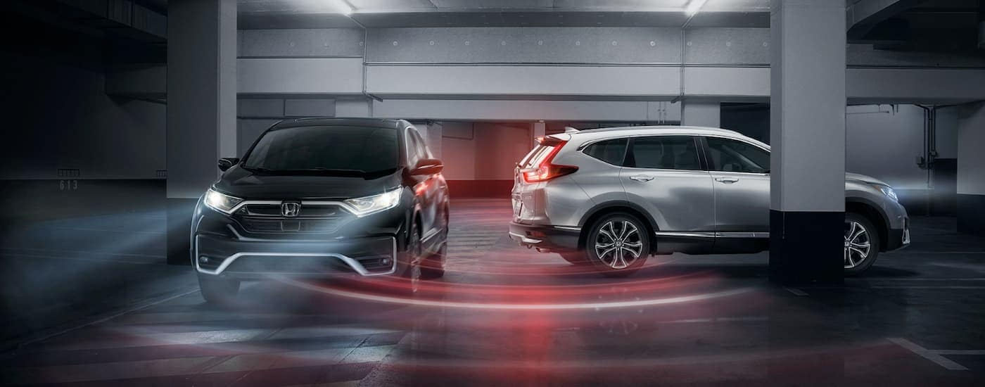 A silver 2020 Honda CR-V Touring is reversing in a parking garage as a dark grey 2020 Honda CR-V Touring drives by.