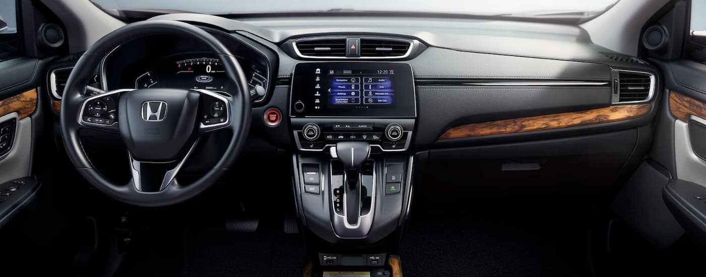The dashboard of 2020 Honda CR-V Touring is shown in dark grey with wood grain details.