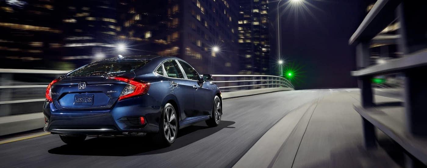 A blue 2020 Honda Civic Sedan is driving on a city street at night.