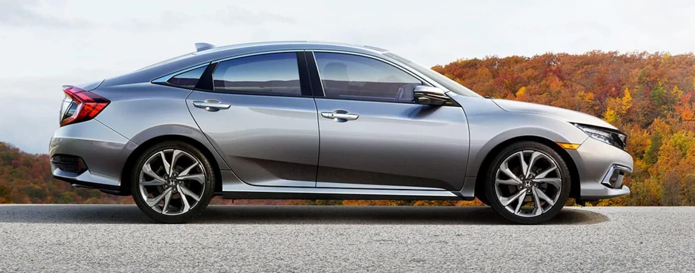 A silver 2020 Honda Civic Sedan Touring is shown from the side parked on a Rochester, NY, road with fall leaves behind it.