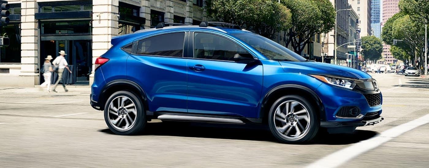 A blue 2020 Honda HR-V Sport is driving on a city street near Rochester, NY.