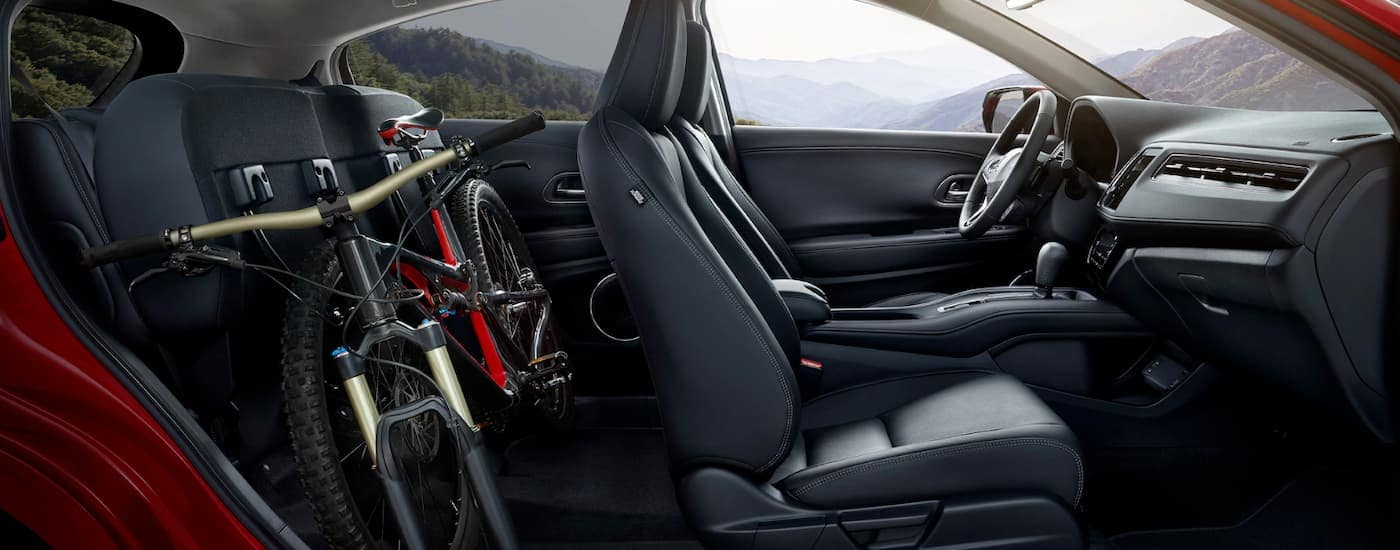 The black interior of a 2020 Honda HR-V Touring is shown from the side with a bike in the back seat.