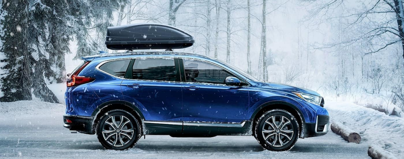 A blue 2020 Honda CR-V AWD Touring is parked in the snow near Rochester, NY.