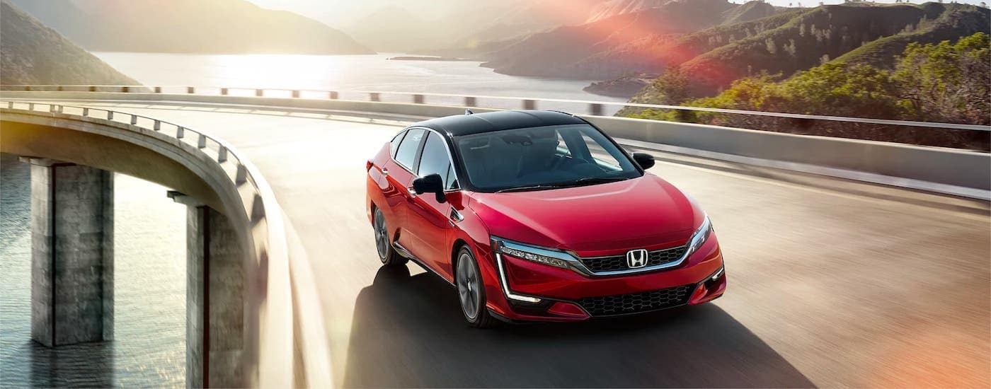 A red 2020 Honda Clarity Fuel Cell driving on a highway in front of a river.