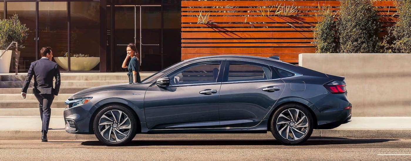 A couple in formal wear walk away from a gray 2020 Honda Insight into a modern building.
