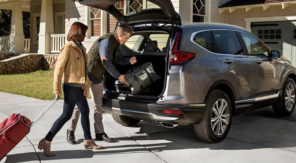 A couple is loading luggage into the back of their grey 2020 Honda CR-V Touring outside of their Rochester, NY home.