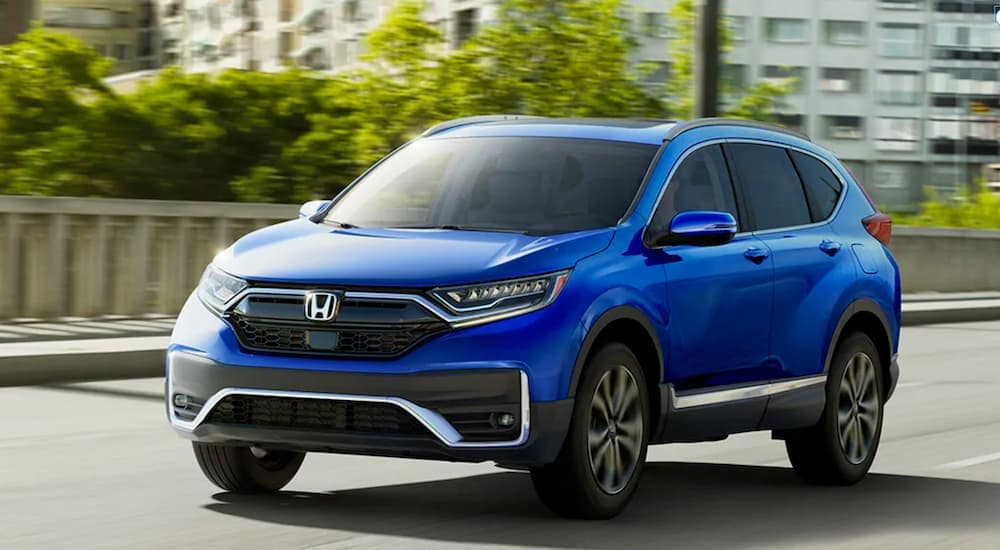 A blue 2020 Honda CR-V Touring is driving on a city street near Rochester, NY.