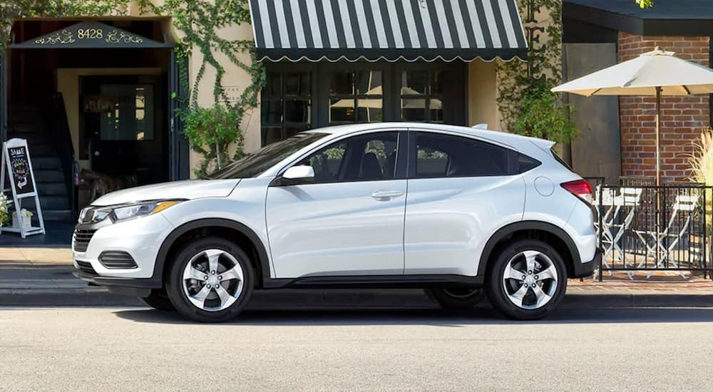 A white 2020 Honda HR-V LX, which is the smallest of the Honda SUVs, is parked on a downtown steet.