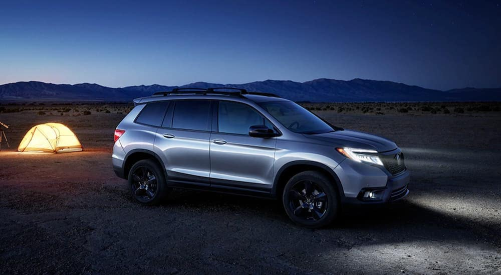 A silver 2020 Honda Passport Elite is parked at a campsite at night.