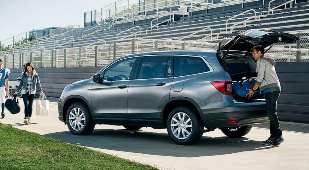 A family is loading gear into a silver 2020 Honda Pilot LX after a football game.