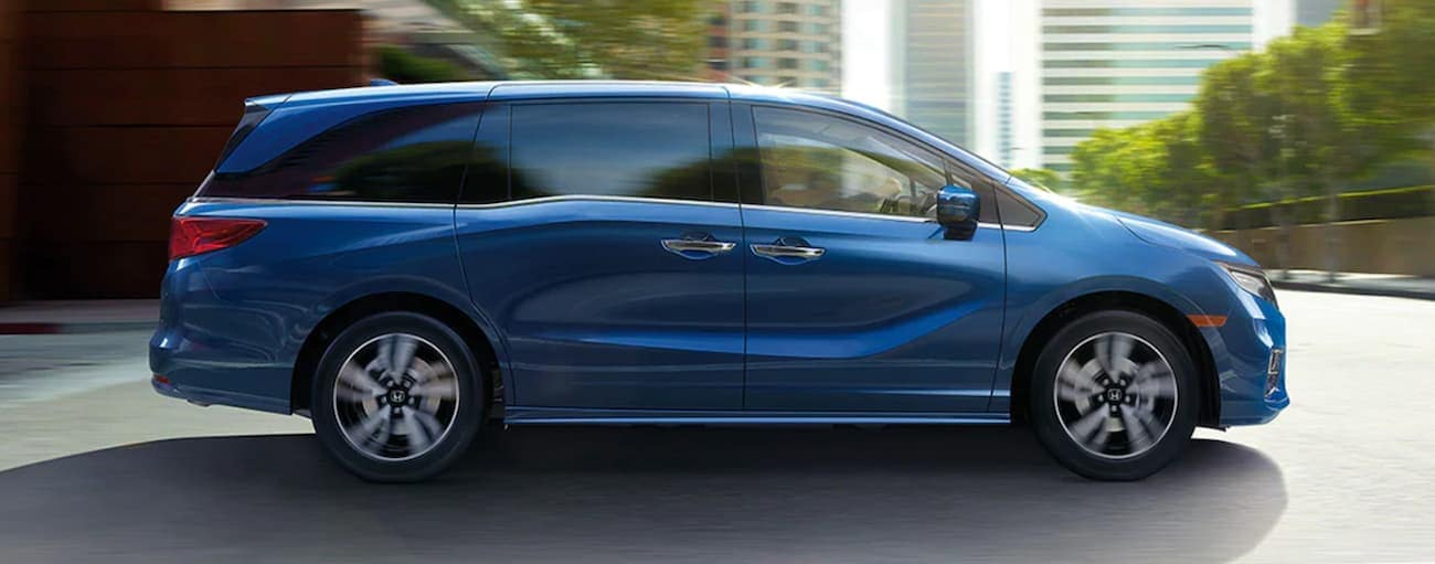 A blue 2020 Honda Odyssey is shown from the side driving through a city.