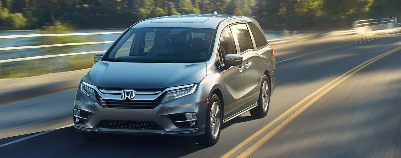 A grey 2020 Honda Odyssey Elite is driving past a pond near Rochester, NY.