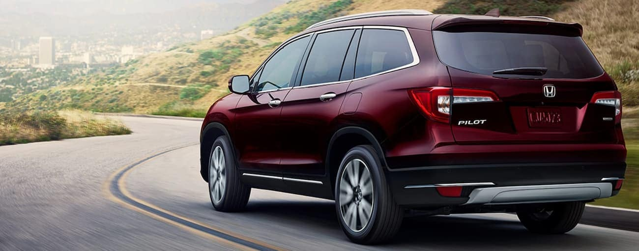 A red 2020 Honda Pilot Touring is driving on a winding road towards a city.