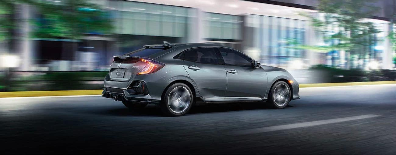 A gray 2020 Honda Civic Hatchback Sport Touring is driving on a city street in Rochester, NY.