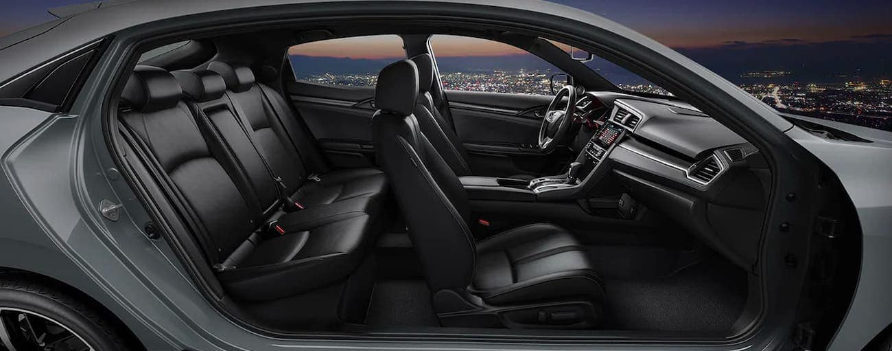 Both passenger-side doors are open, showing the black interior of a 2020 Honda Civic Hatchback Sport Touring.