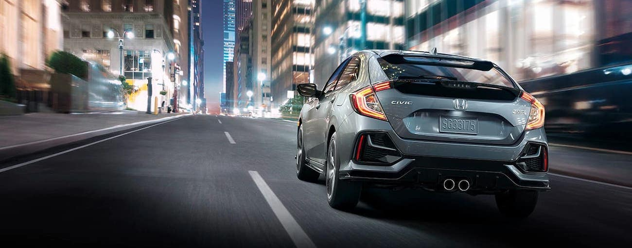 A gray 2020 Honda Civic Hatchback Sport Touring is shown from the rear driving on a city street near Rochester, NY at night.