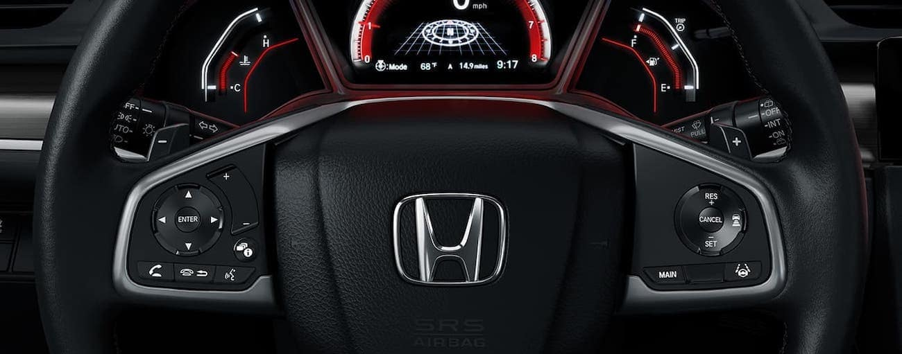 A closeup is shown of the steering wheel and driver information panel in a 2020 Honda Civic Hatchback Sport Touring.